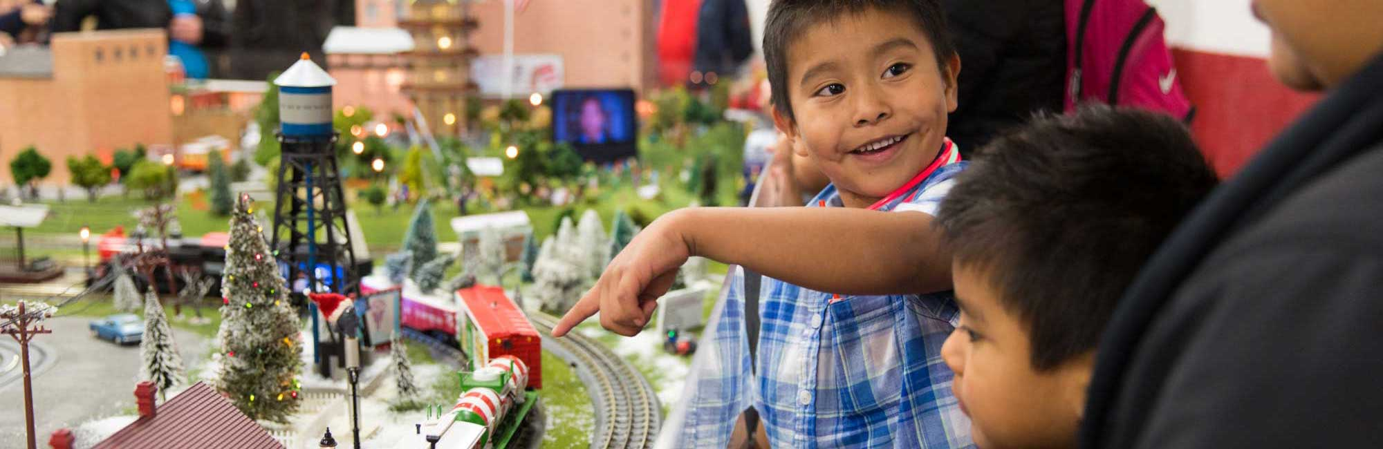 happy child pointing at train garden