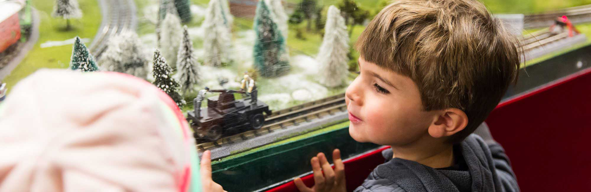 child looks in wonder at toy trains
